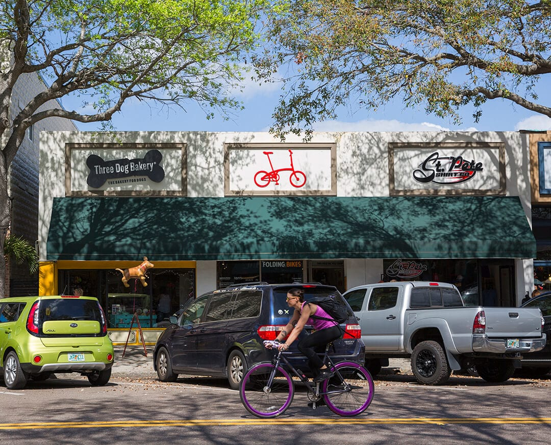 Woman riding bicycle in front of stores on St. Petersburg street.