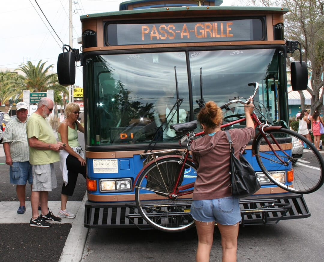 Woman placing bicycle on front of county bus. People stepping into the bus.